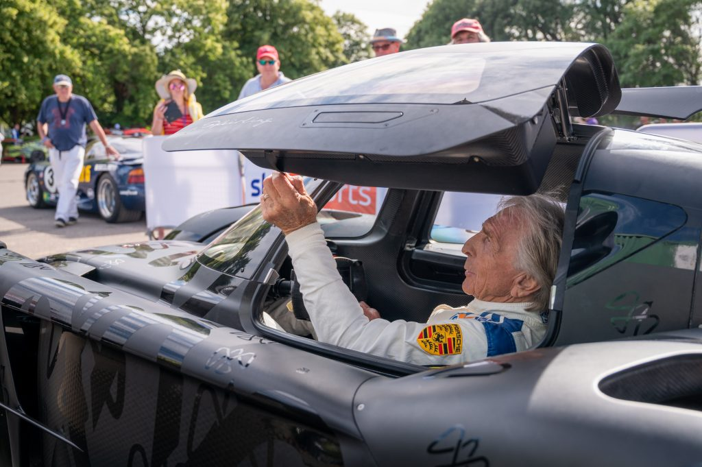 Derek Bell MBE pulls closed the door of the McMurtry Spéirling at the Goodwood Festival of Speed